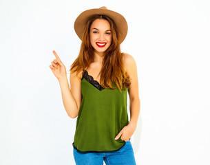 Young stylish girl model in casual summer green clothes and brown hat with red lips got the idea and she put her finger up. Isolated