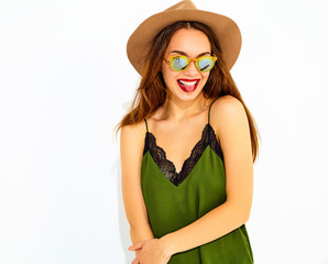 Young stylish girl model in casual summer green clothes and brown hat with red lips, showing her tongue