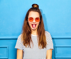 Young stylish girl model in casual summer clothes with red lips, posing near blue wall. Winking and showing her tongue