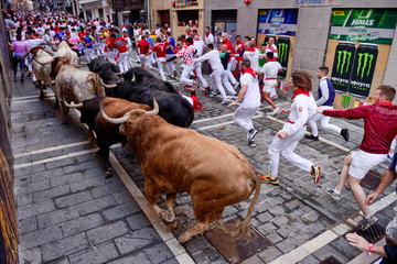 Runners sprint in front of bulls and steers during the fourth running of the bulls of the San Fermin festival in Pamplona