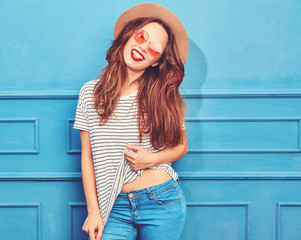 Young stylish girl model in casual summer clothes and brown hat with red lips, posing near blue wall. Showing her tongue