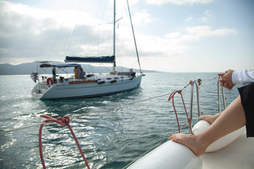 Yachts in the open sea. The coastline is visible. People rest on yachts.