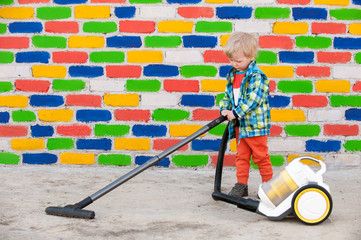 Happy child in bright suit with a vacuum cleaner against background of multi-colored brick wall. Romantic lighting with reflection of sunlight. Lens Flare effect without postproduction