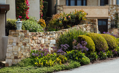Home landscaping example with a garden wall featuring intricate stone work and a varied palette of planting