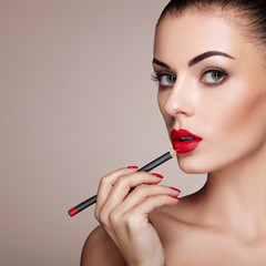Beautiful Woman paints Lips with Lipstick. Beautiful Woman Face. Makeup detail. Beauty Model with Perfect Skin. Red Lips and Nails Manicure