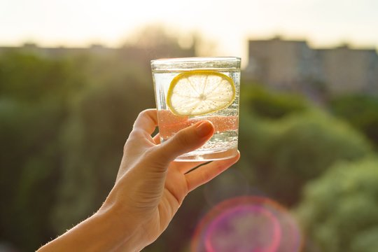 Glass of clear, sparkling water with lemon in hand. Background sky, silhouette of the city, sunset
