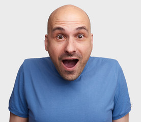 excited bald man isolated over grey background
