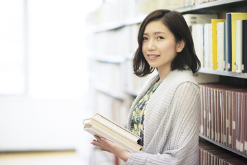 図書館で本を持ち微笑む女性 Wall mural