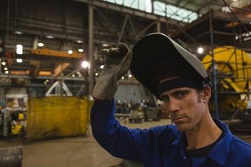 Portrait of confident welder holding welding helmet