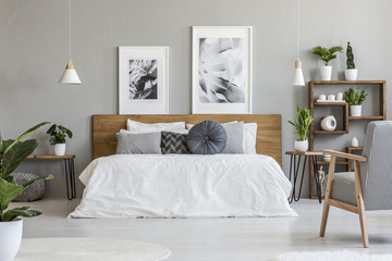 Posters and lamps above wooden bed in grey bedroom interior with patterned armchair. Real photo