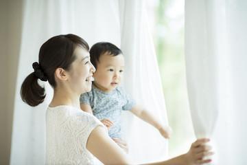子供を抱きカーテンを開ける母親