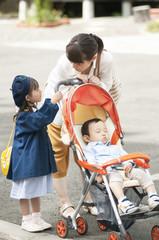 ベビーカーを押す母親と娘