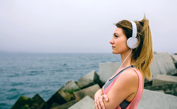 Side view of sportswoman with headphones watching the sea