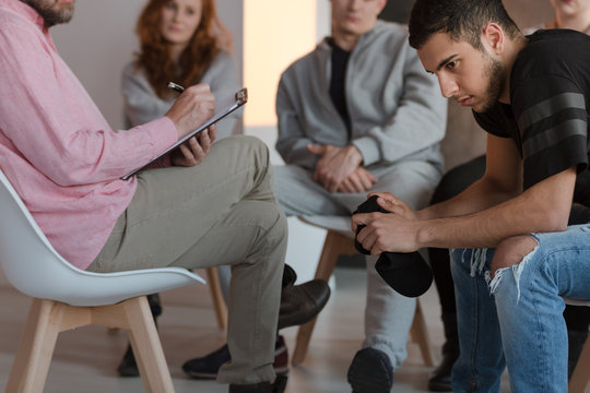 Arrogant teenager sitting at a meeting of support group while his therapist is talking
