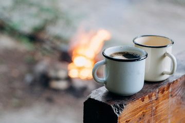 Two coffee cups  near campfire. Warm and cold. Camping.