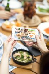 スマートフォンで料理の写真を撮る手元