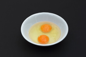 Prepare two chicken eggs in a bowl to cook on black background.