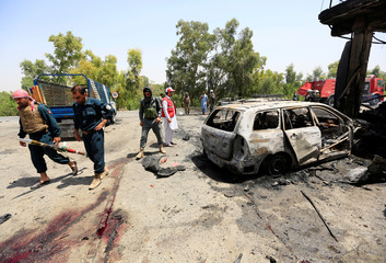 Afghan policemen inspect the site of a suicide attack in Jalalabad city