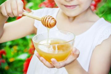 The child eats honey. Selective focus.
