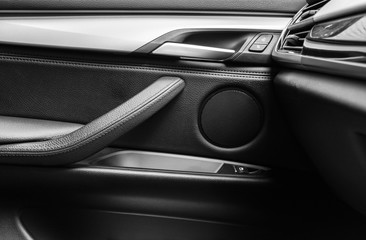 Door handle with Power window control buttons of a luxury passenger car. Black leather interior of the luxury modern car. Modern car interior details. Car detailing. Black and white
