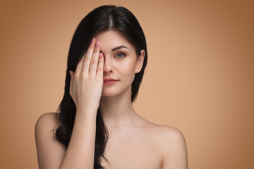 Cute woman covering eye with hand