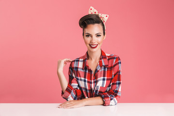 Portrait of a cheerful brunette pin-up girl in plaid shirt