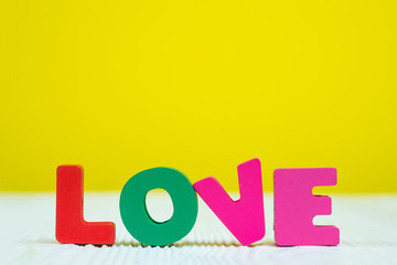 LOVE text alphabet on white wooden table. yellow wall background with copy space.