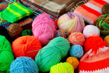 Many colorful balls of yarn for knitting. Multicolored yarn for knitting is gathered in a heap. Knitted clothes, knitting needles and yarn in the background of a plaid.