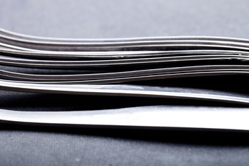Lot of metal cutlery on a black background. Selective focus. Shallow depth of field