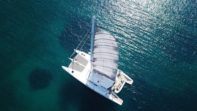 Aerial drone bird's eye view photo from luxury Catamaran docked at tropical deep blue sea