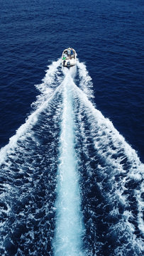 Aerial birds eye view from drone of boat cruising in high speed in turquoise water, island of Mykonos, Cyclades, Greece