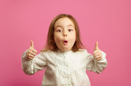 Portrait of emotional little girl showing thumbs up, has surprised expression, opened her mouth, expresses astonishment and unexpected joy, standing on pink isolated background.
