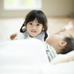 寝ている赤ちゃんに寄り添う女の子