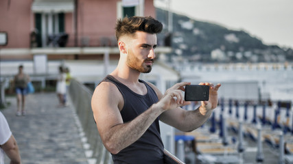 Young handsome man at the seaside using smartphone to take shots and film footage of the sea or ocean