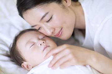眠っている赤ちゃんに頬を寄せる母親