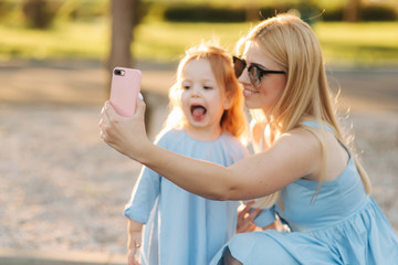 Mom and her little daughter make selfie in the park
