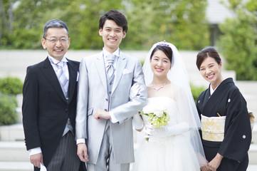 集合して笑顔の新郎新婦と両親