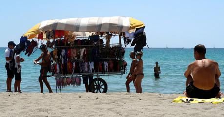 Local police officers check beach vendor's permission at the Poetto beach in Cagliari