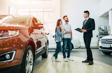 Young modern happy couple buying a new car in city dealership and talking with salesman