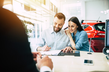 Beautiful happy couple sitting at the table signing a documents for the purchase of a car at the dealership