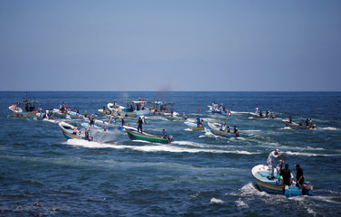 People ride boats as a boat carrying Palestinian patients and students sails towards Europe aiming to break Israel's blockade on Gaza, at the sea in Gaza