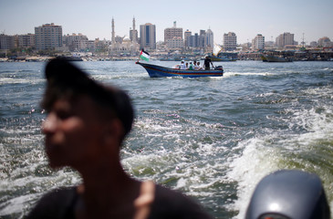 People watch as a boat carrying Palestinian patients and students sails towards Europe aiming to break Israel's blockade on Gaza, at the sea in Gaza