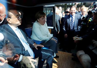 Chinese Prime Minister Li Keqiang and German Chancellor Angela Merkel attend a presentation for autonomous driving inside a Volkswagen car at the Tempelhof airport in Berlin