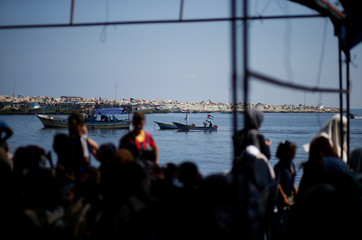 People watch as Palestinians prepare to sail a boat carrying patients and students towards Europe aiming to break Israel's blockade on Gaza, at the sea in Gaza