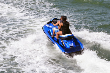 Couple riding tandem on a blue jet ski on the Florida Intra-Coastal Waterway.