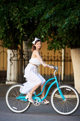 Playful female with a beautiful smile on a vintage bicycle is riding along the city street looking to the side. The girl is dressed in a light dress and an accessory on her head