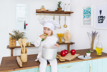 Little beautiful girl in a cook cap sits on a kitchen table with mango and red apples.