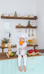 Little beautiful girl in a cook cap sits on a kitchen table and eats big orange fruit.