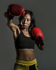 close up portrait of young fit Asian Chinese woman in fitness top and boxing gloves throwing punch in bad girl attitude angry and defiant in combat