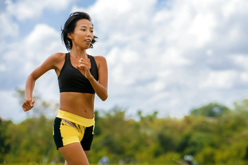 fit and sporty Asian Thai woman with athletic body training outdoors in hard running workout on green field landscape doing jogging workout fitness concept